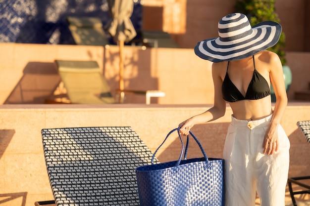 Vrouwen staan in de buurt van zonnebank met strozak om te zonnebaden op het strand. Premium Foto