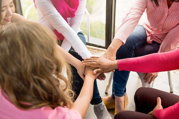 Vrouwen steken hun handen in de vergadering van borstkankerbewustmakingscampagnes Premium Foto