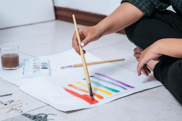 Vrouwen tekenen en schilderen water op papier. Gratis Foto
