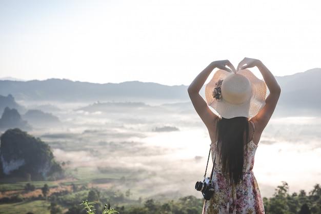 Vrouwen tonen hartvormige gebaren bij het uitkijkpunt op de berg. Gratis Foto