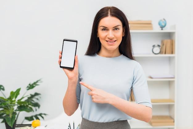 Vrouwen wijzende vinger op smartphone met leeg scherm Gratis Foto