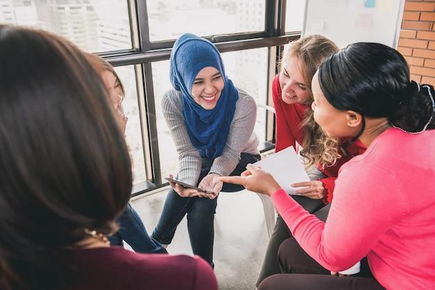 Vrouwen zitten in cirkel genieten van het delen van verhalen in groepsbijeenkomst Premium Foto