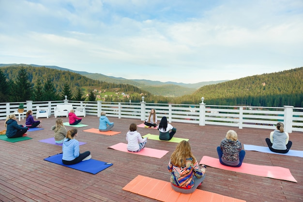 Vrouwen zitten op yogamatten in bergen, oefenen. Premium Foto