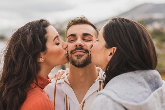 Vrouwen zoenen mannelijke vriend Gratis Foto