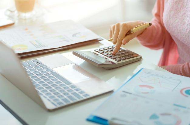 Vrouwenaccountant die aan rekeningen in bedrijfsanalyse werken met grafieken en document financiële gegevensrapport Premium Foto