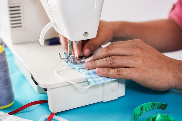 Vrouwenarbeider die naaimachine met behulp van terwijl het maken van gezichts medische maskers tijdens coronavirusuitbraak - naar huis gemaakt productieconcept Premium Foto