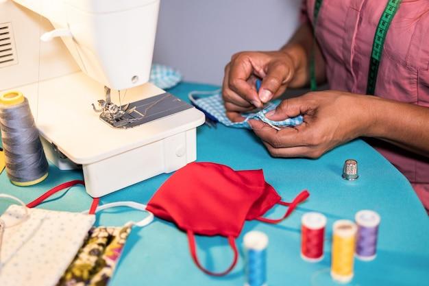 Vrouwenarbeider die naaimachine met behulp van terwijl het maken van gezichts medische maskers tijdens coronavirusuitbraak - naar huis gemaakte rechts conceptn productie Premium Foto