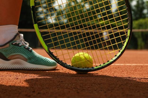 Vrouwenbeen, racket en tennisbal op gravel Premium Foto
