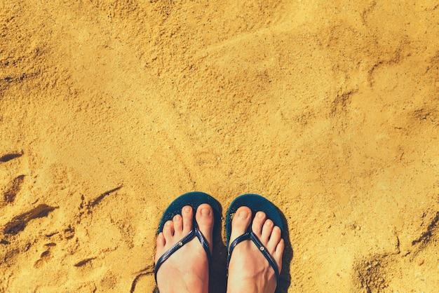 Vrouwenbenen in pantoffels op gele zandachtergrond. blauwe flip-flops op het strand. vakantie- en reisconcept Premium Foto