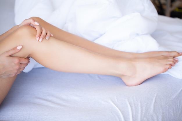 Vrouwenbenen omhoog op de bagage, jonge vrouw die thuis in bed leggen. de witte slaapkamer. Premium Foto
