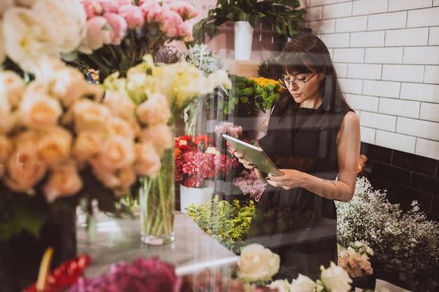 Vrouwenbloemist bij haar eigen bloemenwinkel die bloemen behandelen Gratis Foto