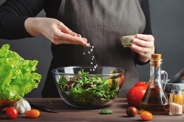 Vrouwenchef-kok in de keuken die salade voorbereiden. Premium Foto