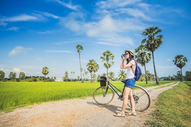 Vrouwenfotograaf die foto voor mening van padieveld nemen door camera. Premium Foto