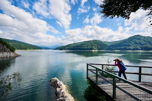 Vrouwenfotograaf met een blauwe rugzak op het meer Premium Foto