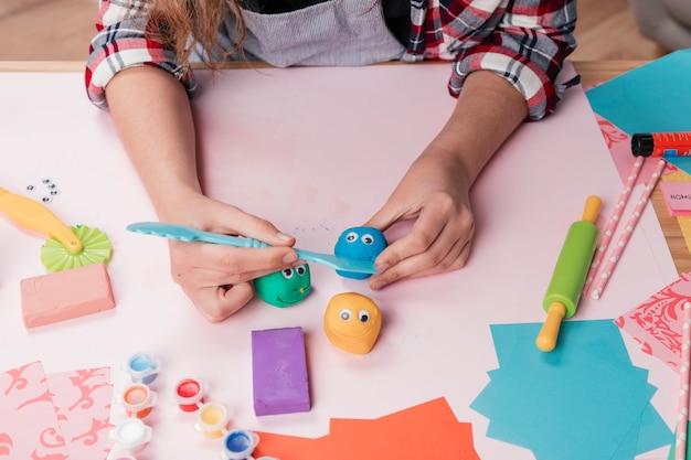 Vrouwenhand die creatieve beeldverhaalgezichten maken die kleurrijke klei gebruiken Gratis Foto