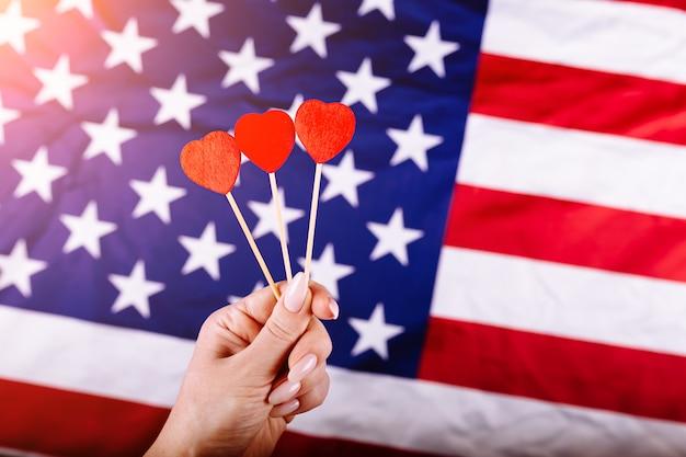 Vrouwenhand die drie rode hartenvorm op stok voor amerikaanse vlag houden Premium Foto