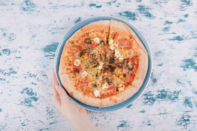 Vrouwenhand die een blauw bord met hete pizza op een marmeren achtergrond houden d. Gratis Foto