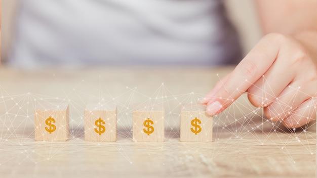 Vrouwenhand die houtsnede met de financiën van de de dollargroei van het pictogramgeld en investeringsconcept schikken. Premium Foto