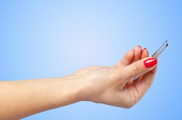 Vrouwenhand die kosmetisch hulpmiddel houden dat op kleurenachtergrond wordt geïsoleerd Premium Foto