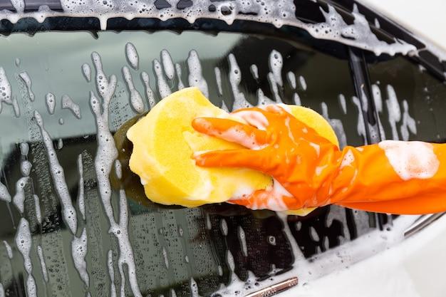 Vrouwenhand die oranje handschoenen met gele spons dragen die zijspiegel moderne auto wassen Premium Foto
