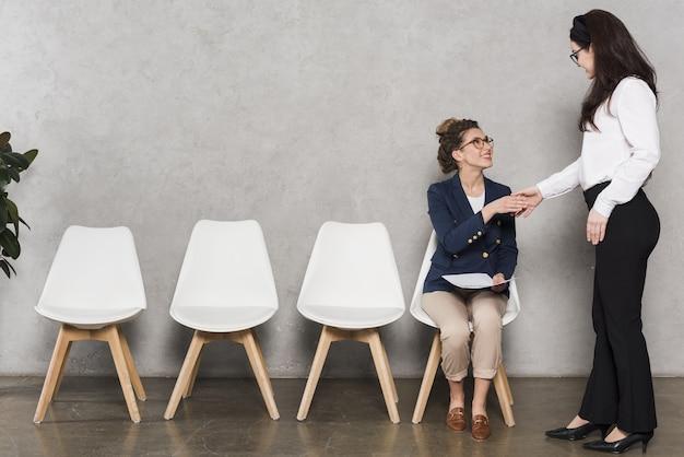 Vrouwenhand die potentiële werknemer schudden vóór baangesprek Premium Foto
