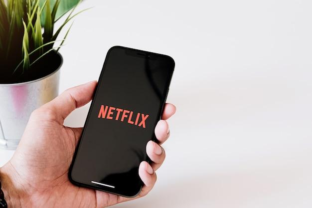 Vrouwenhand die slimme telefoon met netflix-logo op iphone xs houden. netflix is een wereldwijde aanbieder van streaming films en tv-series. Premium Foto