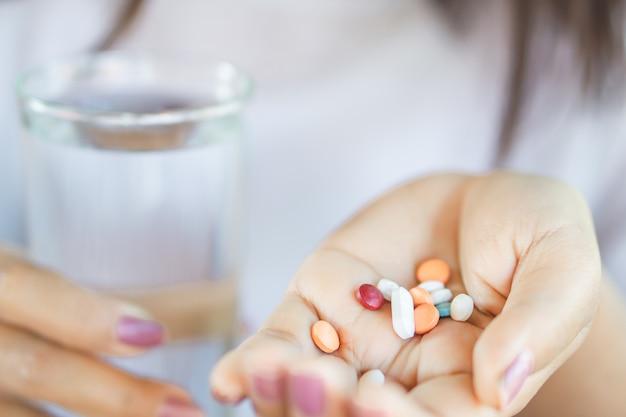 Vrouwenhand die vitaminen met water nemen Premium Foto
