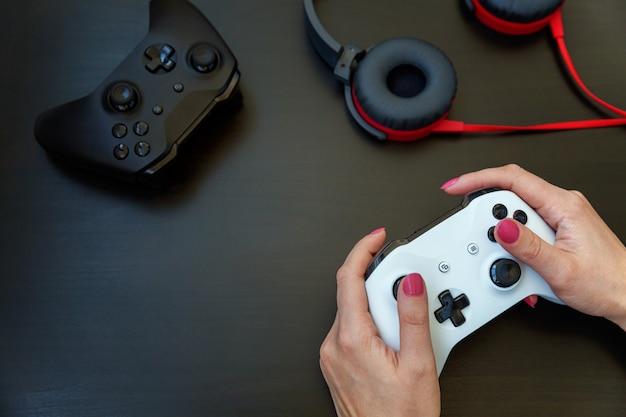 Vrouwenhand die witte bedieningshendel gamepad, spelconsole houden die op zwarte wordt geïsoleerd. Premium Foto