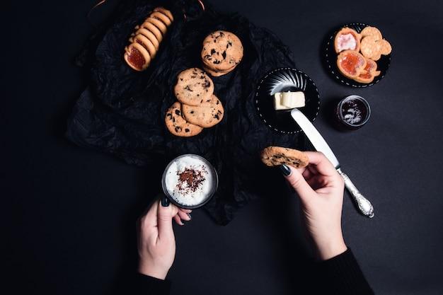 Vrouwenhand met kop koffie of cappuccino en chocoladekoekjes, koekjes Premium Foto
