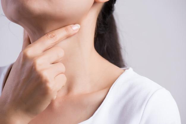 Vrouwenhand wat betreft haar zieke hals Premium Foto