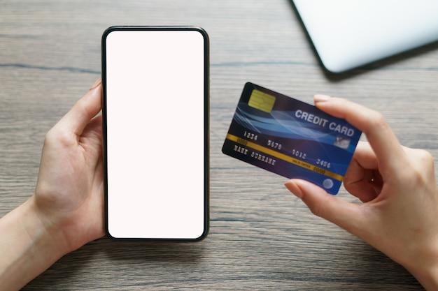 Vrouwenhanden die creditcard en het smartphone lege scherm houden Premium Foto