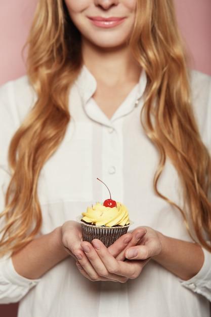 Vrouwenhanden die een heerlijke yummy cupcake houden Gratis Foto