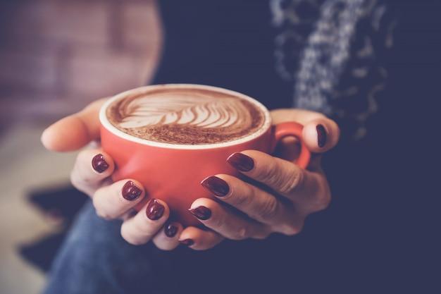 Vrouwenhanden die rode kop van koffie latte houden Premium Foto