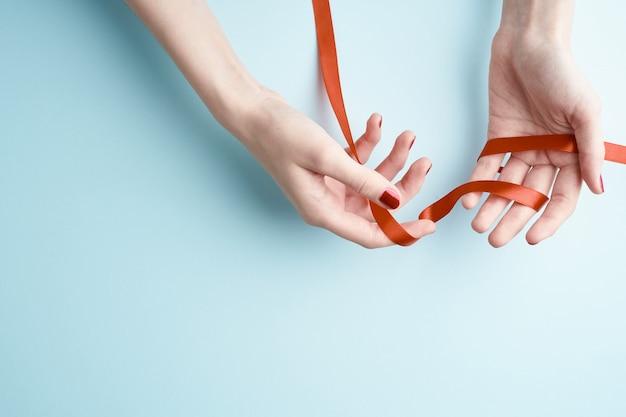 Vrouwenhanden die rood lint houden Premium Foto