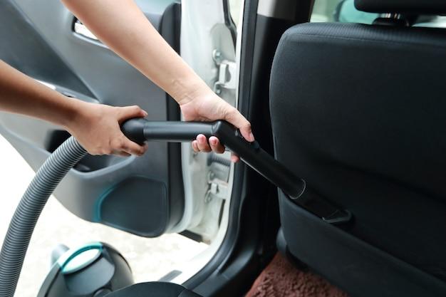 Vrouwenhanden die stofzuiger binnenlandse auto met behulp van Premium Foto