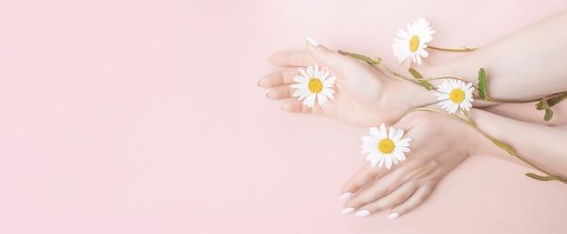 Vrouwenhanden met bloemen. natuurlijke schoonheid handcosmetica met bloemextract, product Premium Foto