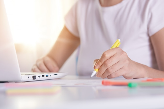 Vrouwenhanden met gele pen die iets schrijven op peper, online werkend, wijfje dat aan laptop werkt Gratis Foto