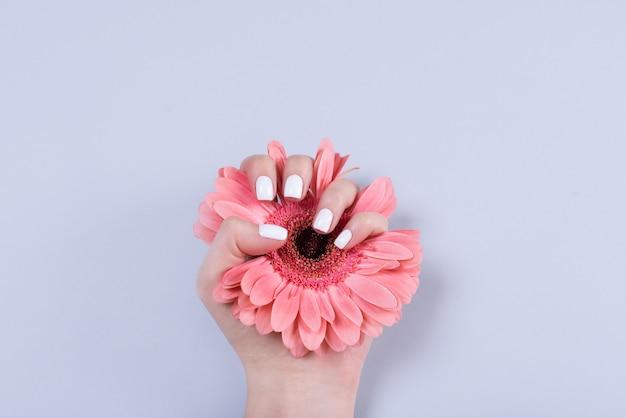 Vrouwenhanden met manicure en trouwring onder wit kant en kleine bloemen Premium Foto