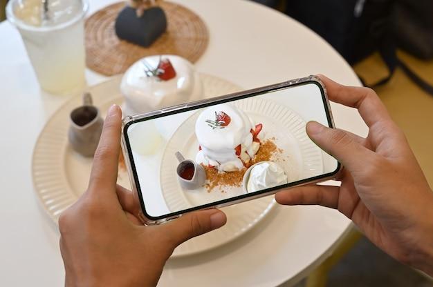 Vrouwenhanden neemt fotografie van dessert met telefoon. pannenkoek en aardbei met room. Premium Foto