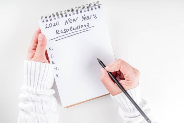 Vrouwenhanden schrijven nieuwjaarsdoelen Premium Foto