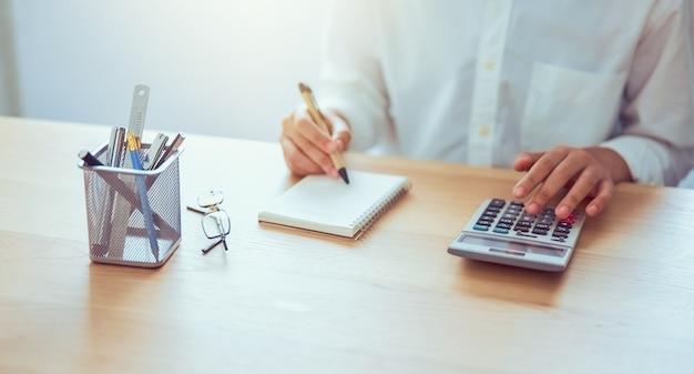 Vrouwenholding en perscalculator om inkomensuitgaven en plannen voor zakgeld aan huisbureau te berekenen. Premium Foto