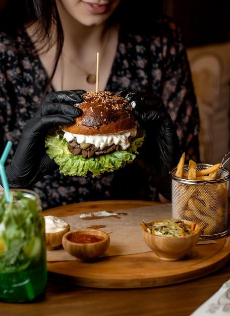 Vrouwenholding met de zwarte hamburger van het handschoenenrundvlees met paddestoel, sla en kaas Gratis Foto