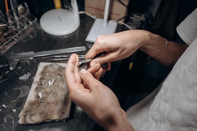 Vrouwenjuwelier snijdt een stuk soldeer af met een kniptang Gratis Foto