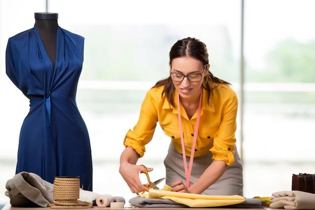 Vrouwenkleermaker die aan nieuwe kleding werken Premium Foto