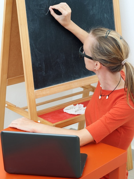 Vrouwenleraar conducts training online met laptop. Premium Foto