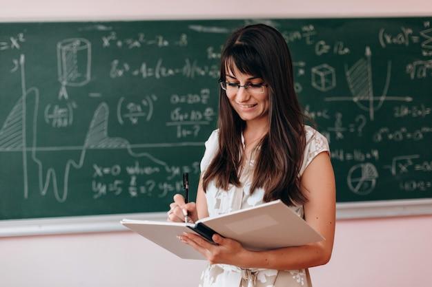 Vrouwenleraar die een studieboek houdt en daarin schrijft. Premium Foto