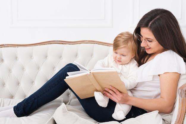 Vrouwenlezing met baby op bank Gratis Foto