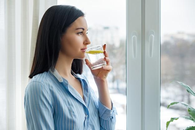 Vrouwenochtend dichtbij het venster drinkwater met citroen Premium Foto
