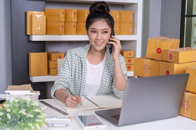 Vrouwenondernemer die met klant op mobiele telefoon spreken en de orde van de productorde thuis kantoor schrijven Premium Foto
