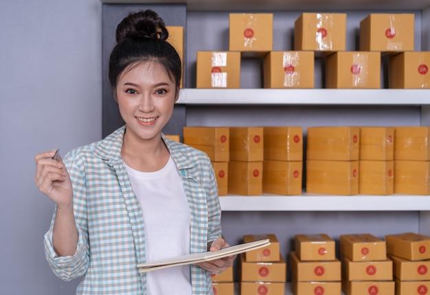 Vrouwenondernemer met pakketdozen in haar eigen baan die online zaken thuis winkelt Premium Foto